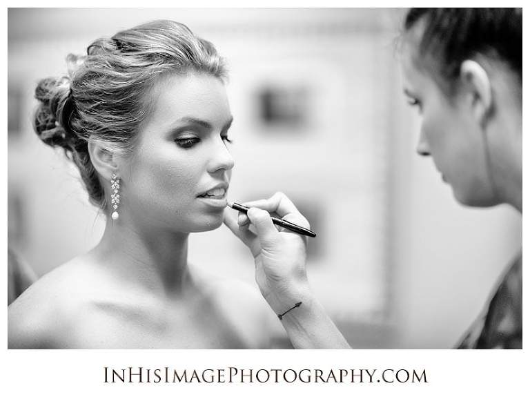 Bride having lipstick applied prior to wedding