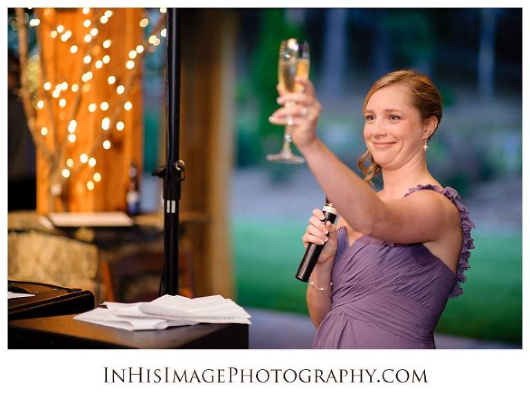 Bridesmaid raises glass during wedding reception toast